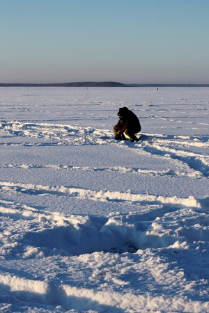 Fisherman sitting on ice photo