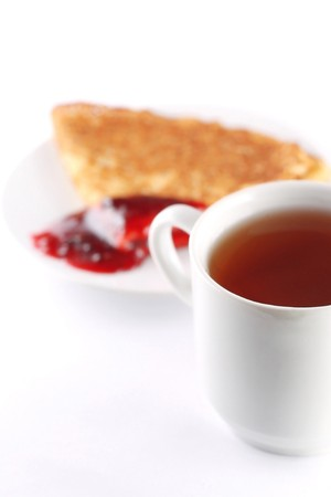 Pancake with red jam on dish and tea cup photo