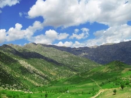 Green meadows between high rocky mountains photo
