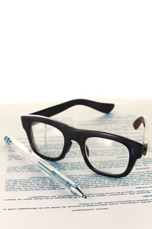 Eye-glasses with paper and pen photo
