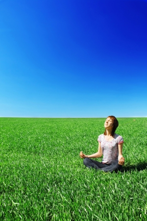 horizon over land: Young woman sitting on green meadow