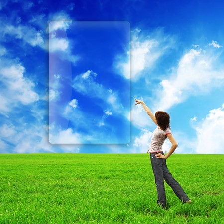 Young woman standing in field with green grass photo