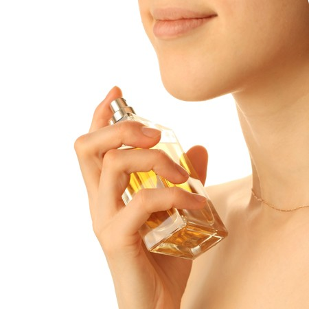 Young woman with yellow perfume bottle photo