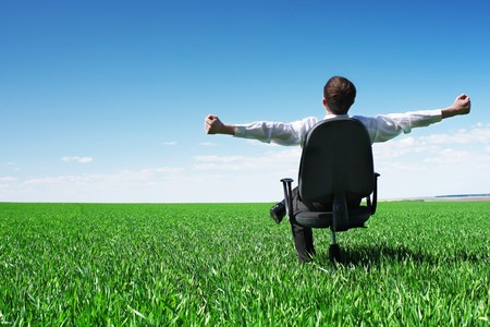 green office: Young businessman sitting on chair in green field
