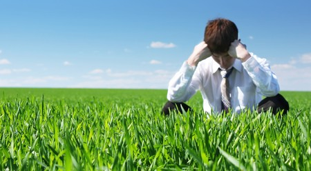 Young sad businessman sitting on green grass Stock Photo