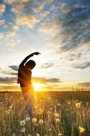 mujer meditando: Mujeres jóvenes, haciendo ejercicios de campo con hierba bajo luz sunset