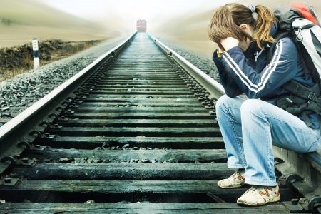 Young woman sitting on railway with comming train