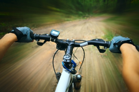 road bike: Riding on a bike in forests path Stock Photo