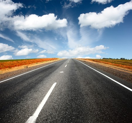 high street: Asphalt road and blue sky with clouds Stock Photo