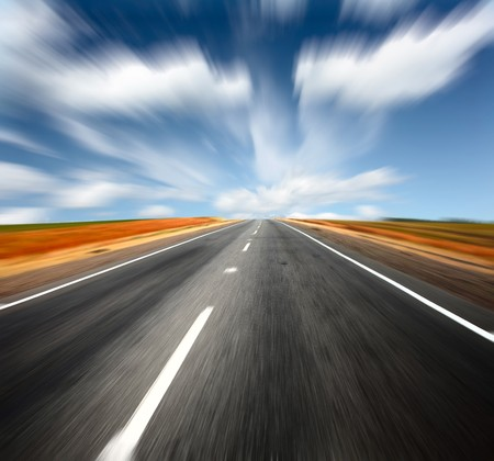 Blurred asphalt road and blue sky with blurred clouds photo