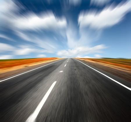 asphalt road: Blurred asphalt road and blue sky with blurred clouds
