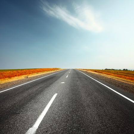 Route asphaltée et ciel bleu avec nuages