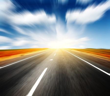 light speed: Carretera asfaltada borrosa y cielo azul con nubes  Foto de archivo