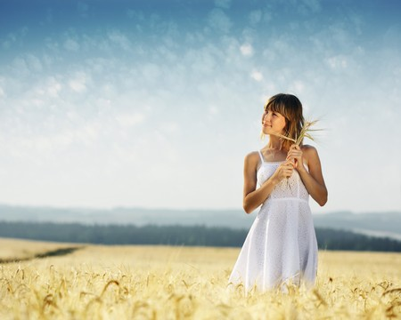 Young smiling woman in white dress standing in field photo
