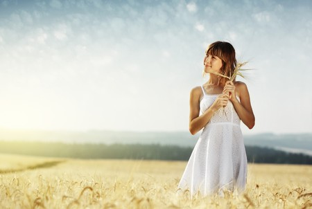 Young smiling woman in white dress standing in field Stock Photo