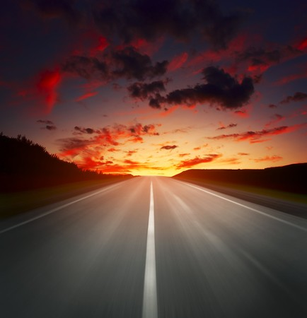 Blurred asphalt road and sky with red clouds photo