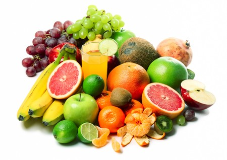 Ripe tropical fruits and slices and glass with juice photo