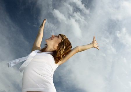 Young smiling woman with raised hands over blue sky Stock Photo - 7600104