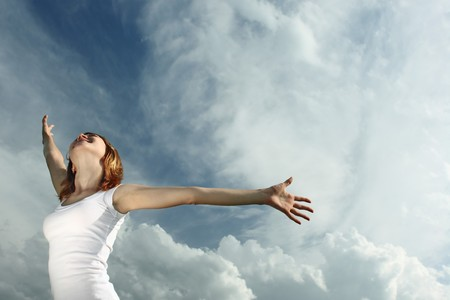 Woman in white with raised hands over airy sky backgroud Stock Photo