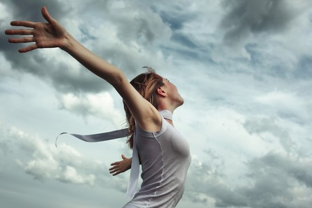 enjoy space: Young woman in white shirt with rised hands over stormy cloudscape