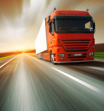 moving truck: Red truck on blurry asphalt road and motion blured sky Stock Photo