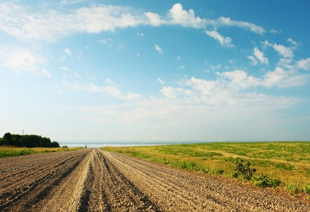 Rural gravel road and blue sky with clouds Stock Photo - 7600163
