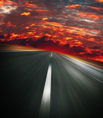 Carretera asfaltada borrosa y rojo cielo sangriento