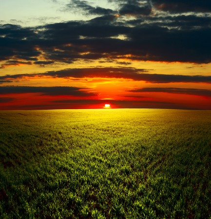 over hill: Cloudy sunset over field with grass Stock Photo