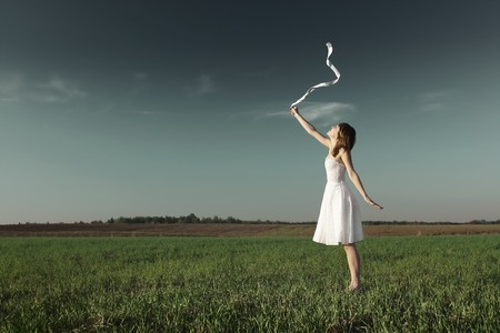 front side: Young woman in white dress with white ribbon standing on grass over dark sky background Stock Photo