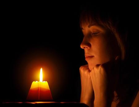 femme triste: Jeune femme souhaitant une bougie.  Banque d'images