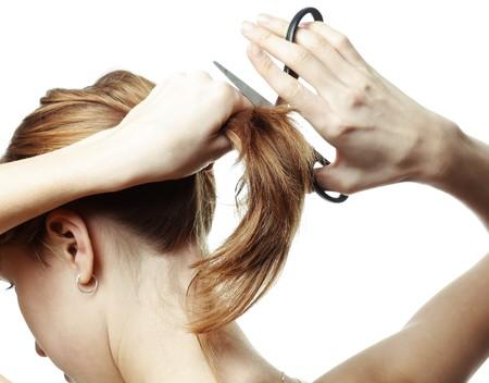 cola mujer: Mujer joven con tijeras va a cortar su pelo