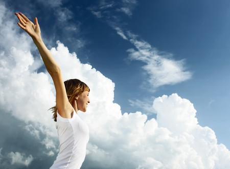 Young woman in white shirt over blue sky with fluffy clouds photo