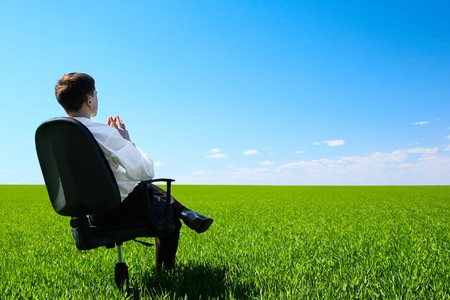 Young man sitting on chair in green meadow photo