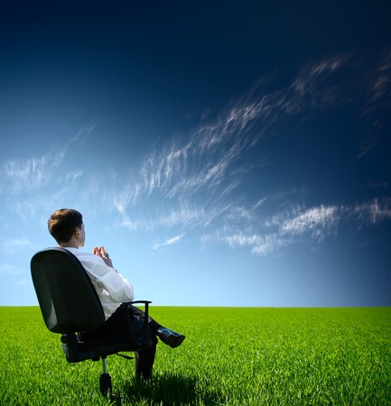 Young man sitting on chair in green meadow and looking to a blue sky with clouds Stock Photo - 7634666