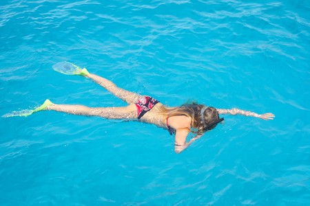 Young woman swimming in clear blue water photo