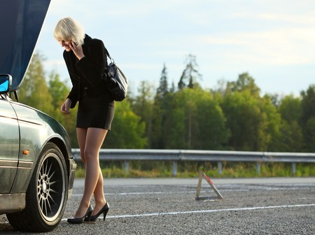 summer tire: Young woman talking on mobile phone near broken car Stock Photo