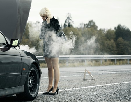 Young woman talking on mobile phone near broken and smoking car Stock Photo - 7634690