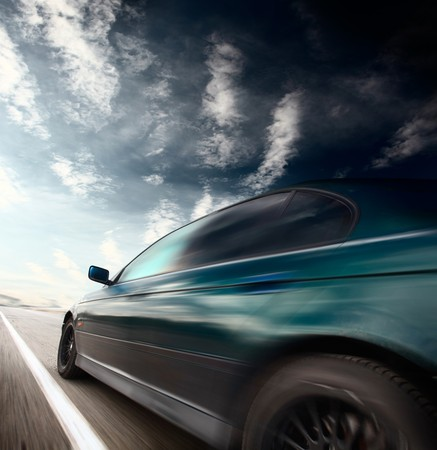 tilt views: Motion blurred car on asphalt road and sky with clouds Stock Photo