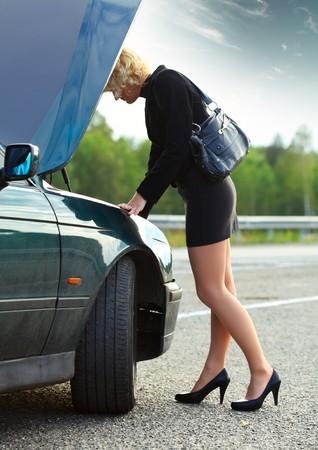 poblíž: Young woman in dress near broken car