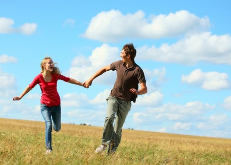 Young laughing couple running on meadow holding each other hands photo