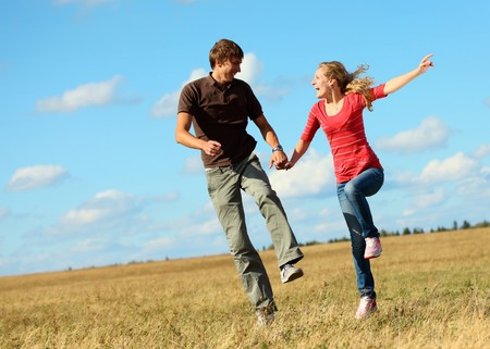 Young laughing couple jumping on meadow holding each other hands photo