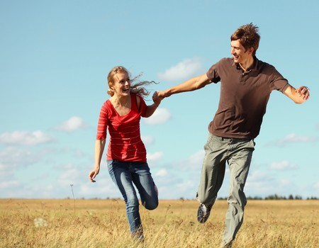 Young smiling couple running on meadow holding each other hands