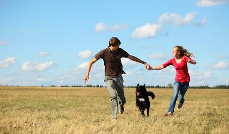 mujeres corriendo: Joven pareja que se ejecutan juntos en pradera con perro