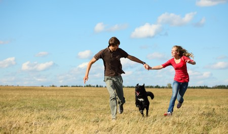 Young couple running together on meadow with dog photo