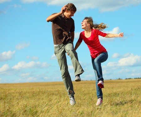 Young laughing couple jumping on meadow holding each other hands Stock Photo