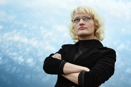 authoritative woman: Serious blonde young woman in glasses on blue sky background Stock Photo