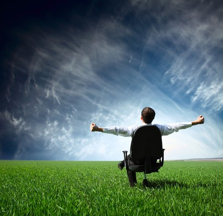 Young man sitting on chair in green meadow Stock Photo - 7791339