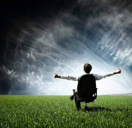 Young man sitting on chair in green meadow Stock Photo - 7791330