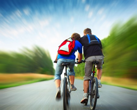 blurr: Two riders with backpacks on bikes riding on an rural asphalt roar. Motion blurred