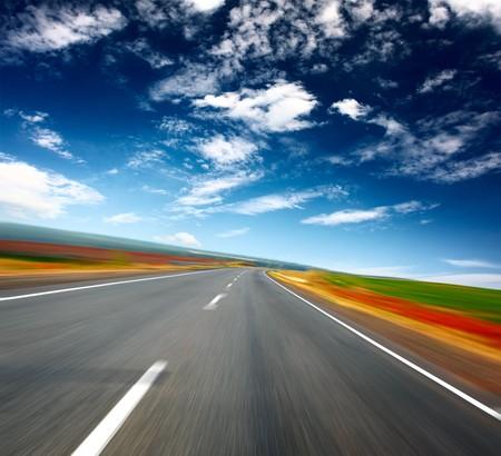 Wazig asfalt weg en blauwe hemel met wolken  Stockfoto